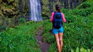 Woman standing on hiking trail to waterfall