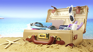 Suitcase filled with beach items in the sand